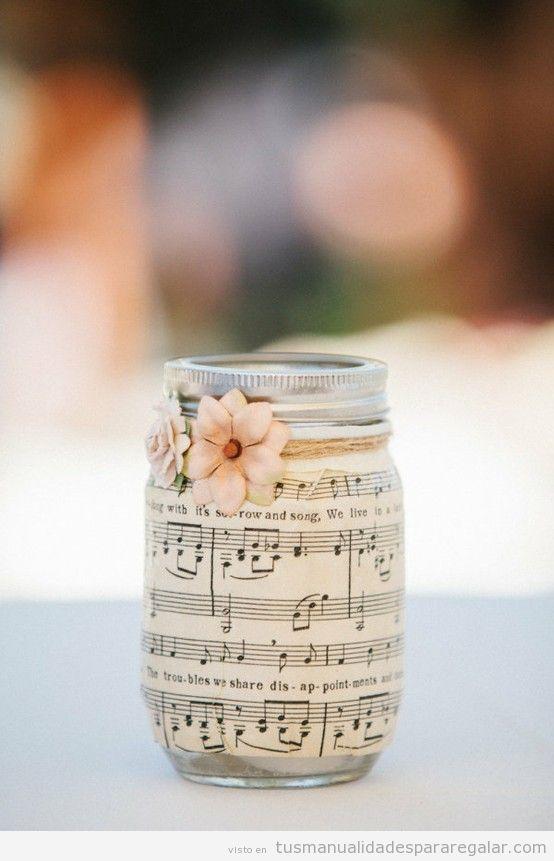 Bote de cristal forrado de partitura y con flores
